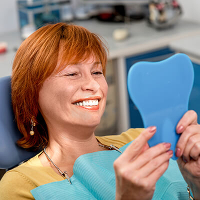 A mature woman, in the dental office looking in the mirror while smiling