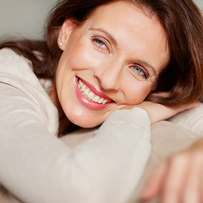 A woman smiling while leaning on her hands